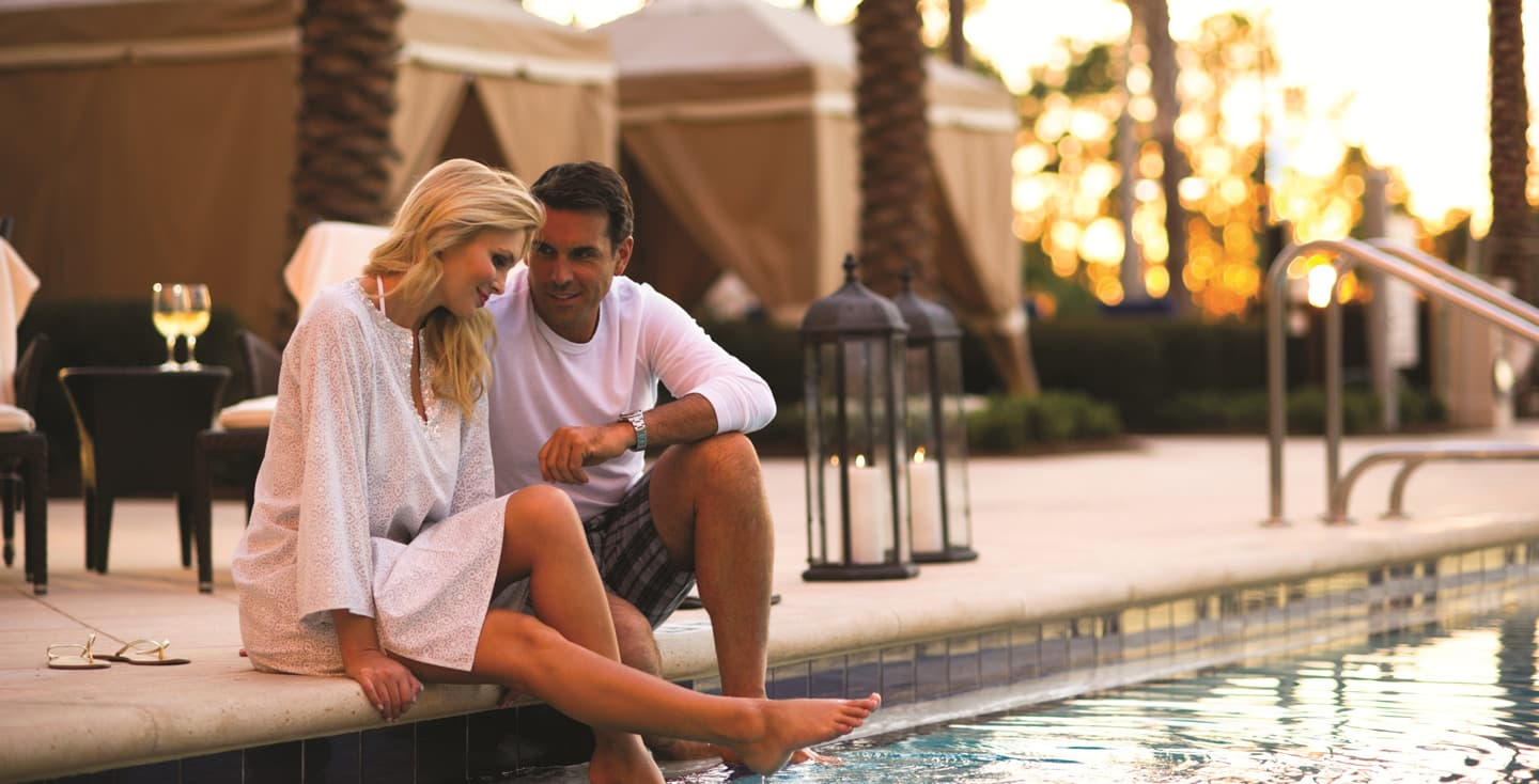 Couple lounging by the Waldorf private cabana pool
